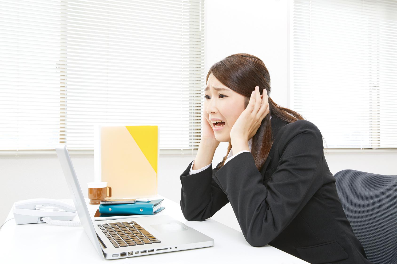 ノートパソコンを見て頭を抱えるビジネスウーマン