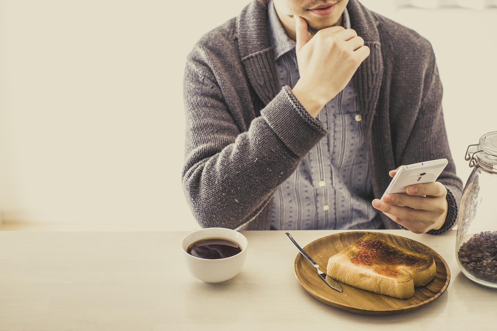 朝食を食べながらスマートフォンを操作している日本人男性