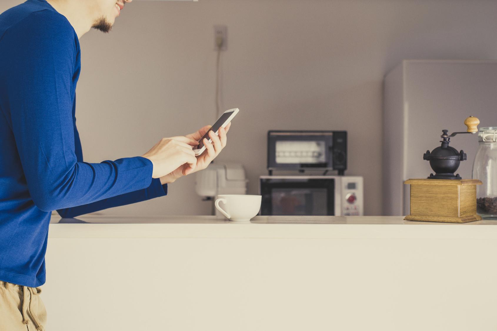 カウンターキッチン,男性とスマートフォン