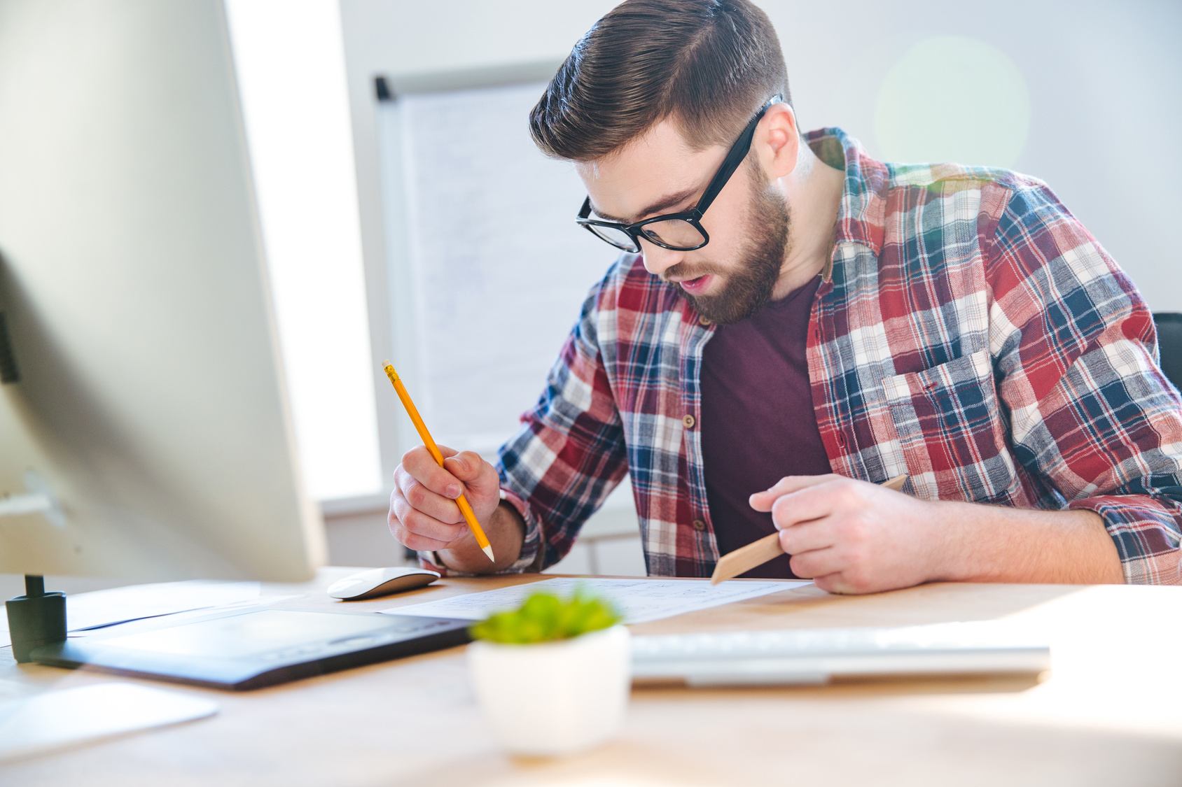 Handsome concentrated young man with beard working with blueprint using ruler and pencil in office