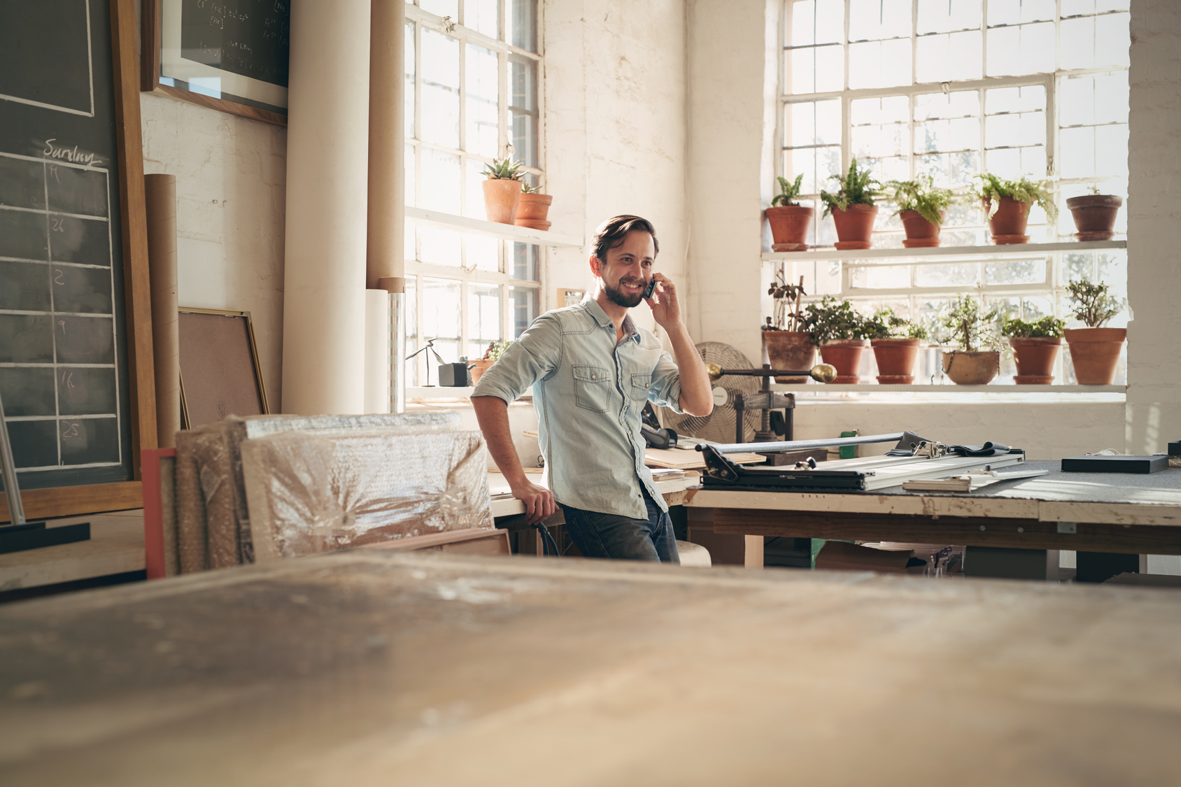 Handsome craftsman standing casually in his workshop studio talking on his phone with a positive expression
