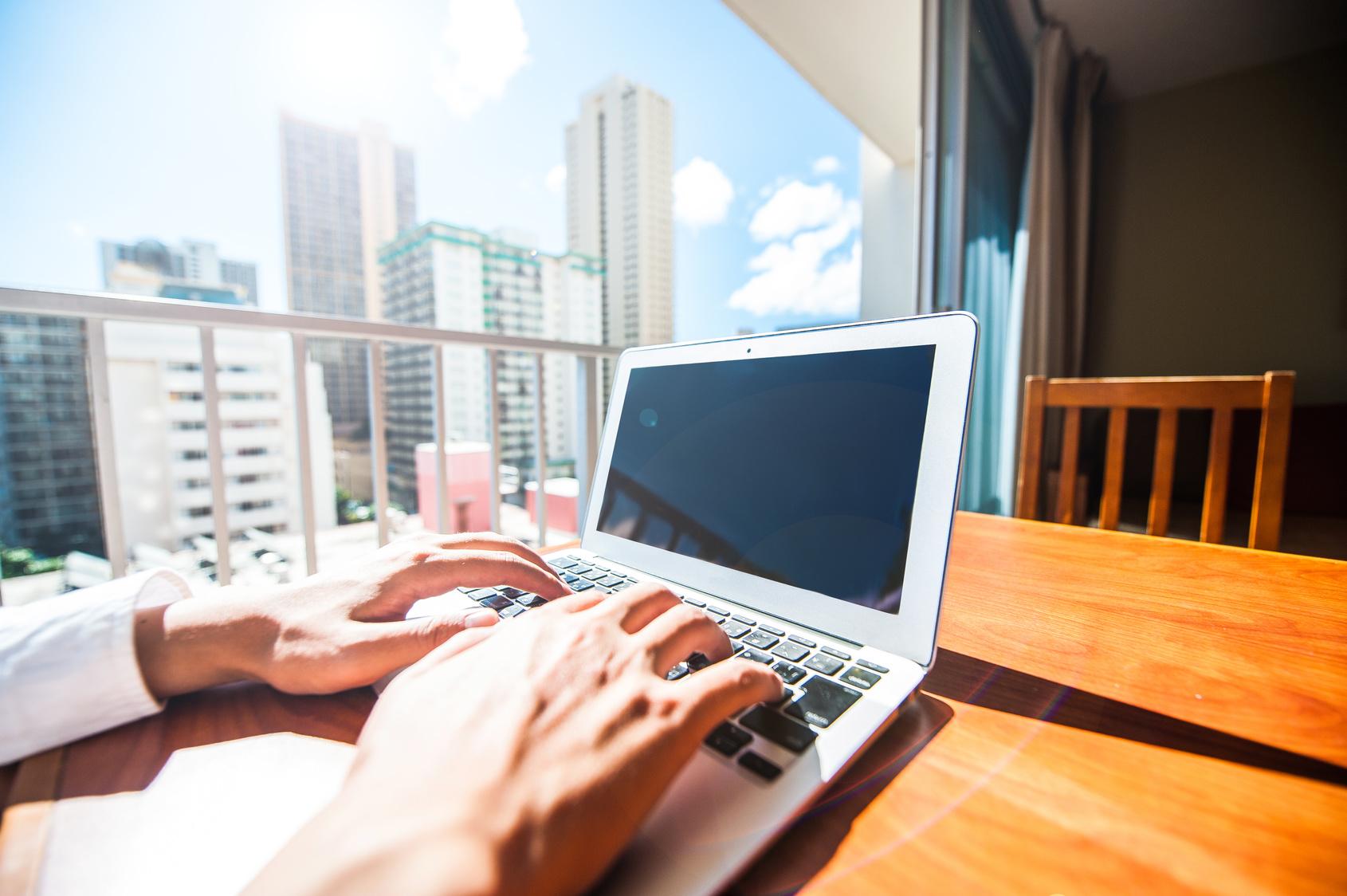 窓際でノートパソコンを使っているビジネスマン