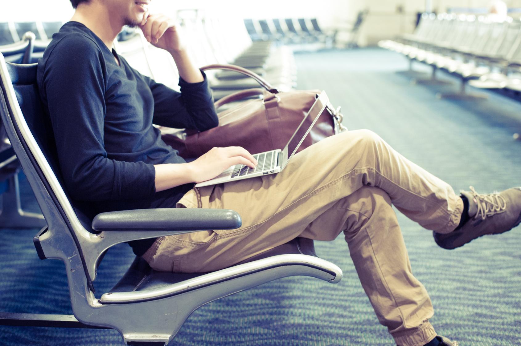 空港の待合室でノートパソコンを使っている男性