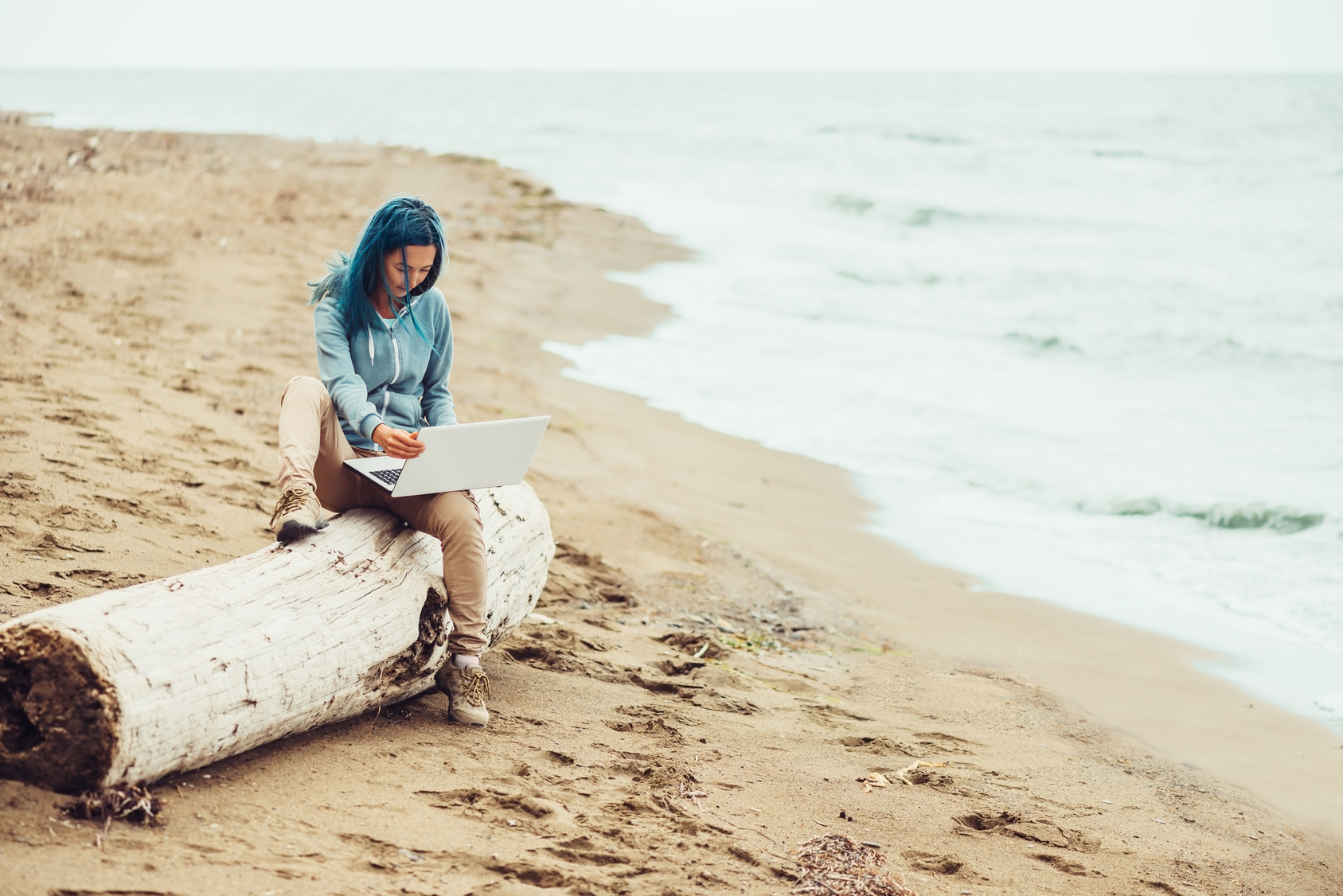 Freelancer young woman with blue hair sitting on tree trunk and working on laptop on sand beach near the sea. Freelance concept