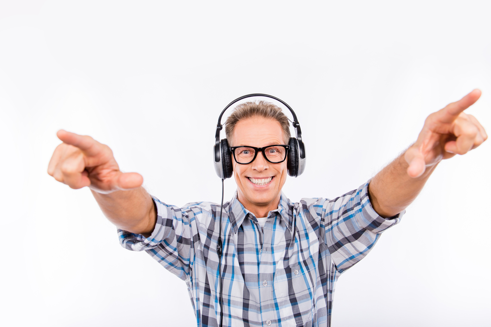 Handsome cheerful aged hipster in glasses with headphones pointing away