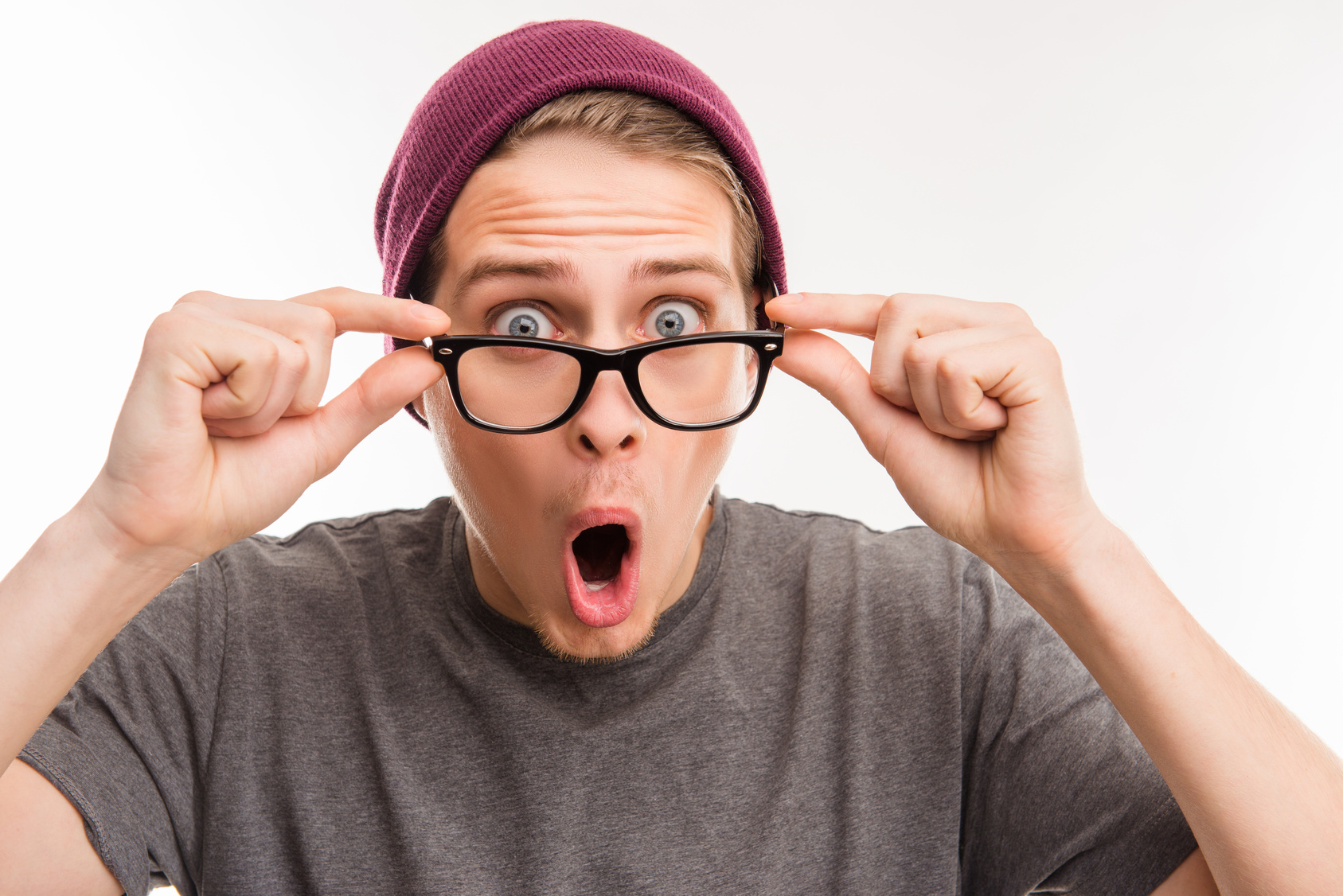 Surprised young hipster in violet cap and glasses with opened mouth