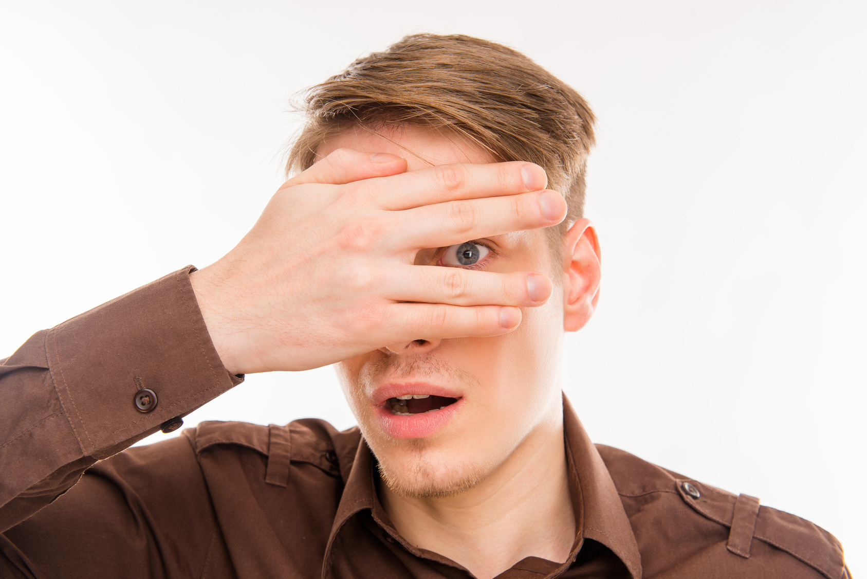 Surprised young man hiding eyes behind his hand