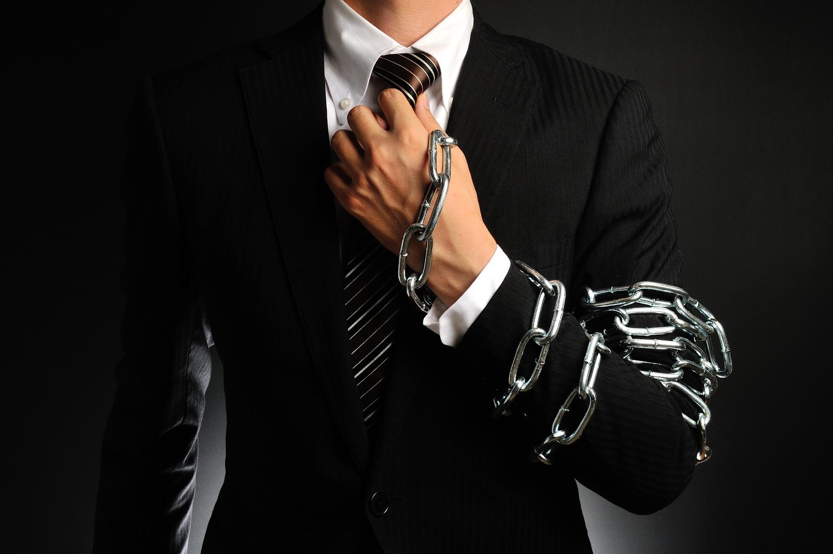 手を鎖で縛られたビジネスマン