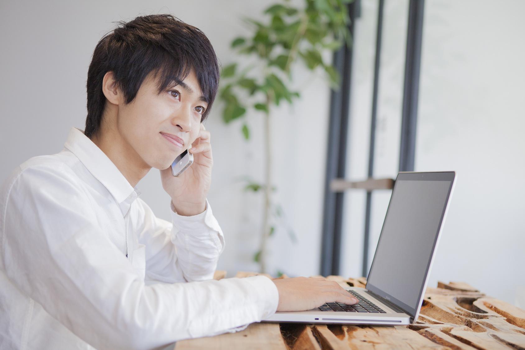 カフェでパソコンを開いて電話をかける男性