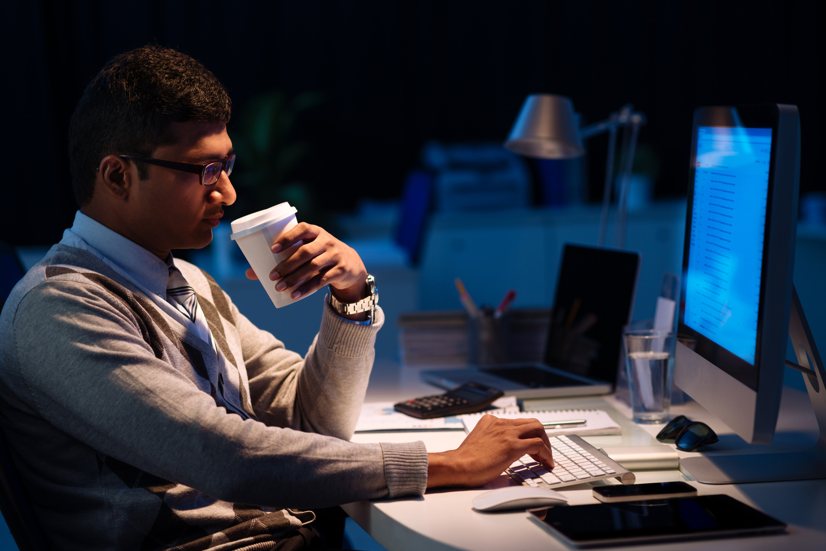 Programmer drinking coffee and computing at night, side view
