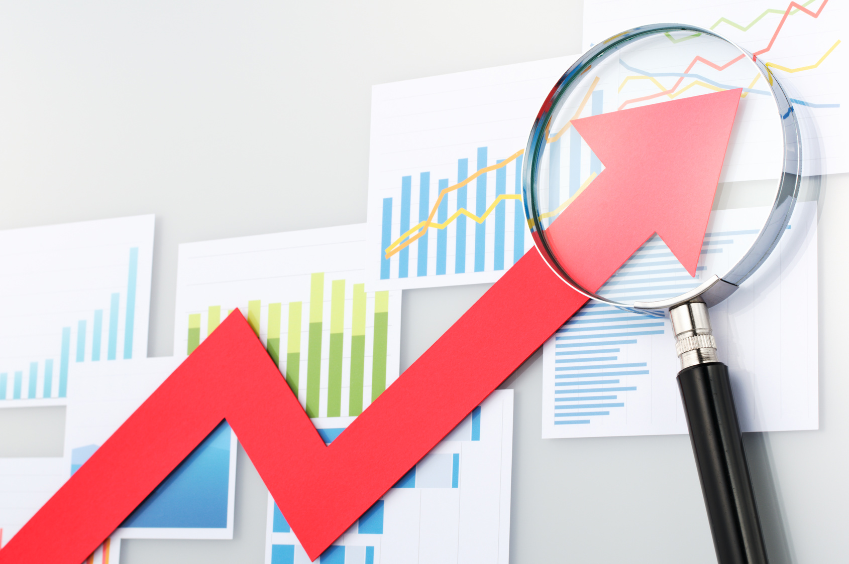 Red arrow and magnifying glass on the background of graphs and charts.