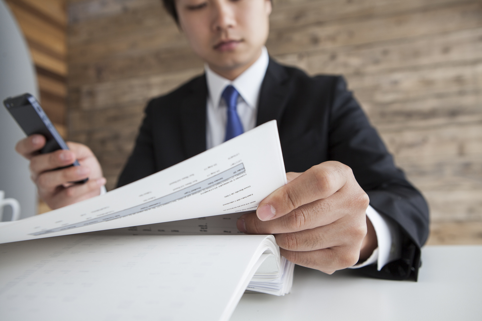Businessman looking at documents with a smartphone