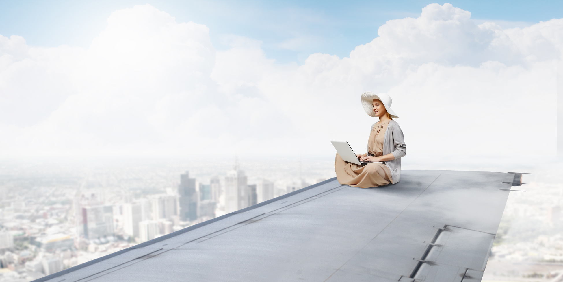 Woman in dress and hat sitting on airplane wing and working on laptop